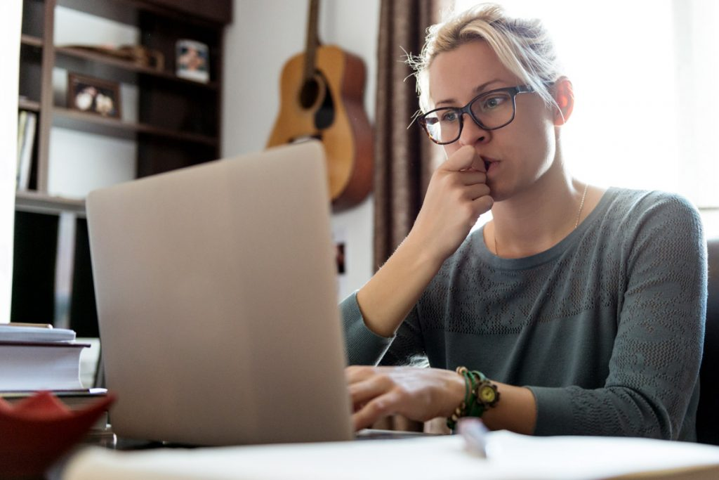 A woman looks perplexed as she looks at her laptop screen.